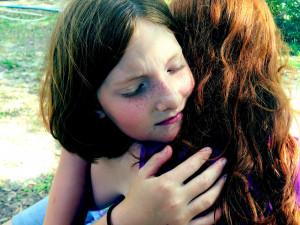 Mutter umarmt ihre Tochter nachdem sie laut geworden ist.
