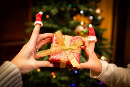 Geschenkübergabe vor dem Weihnachtsbaum als Symbol für richtiges Schenken an Weihnachten